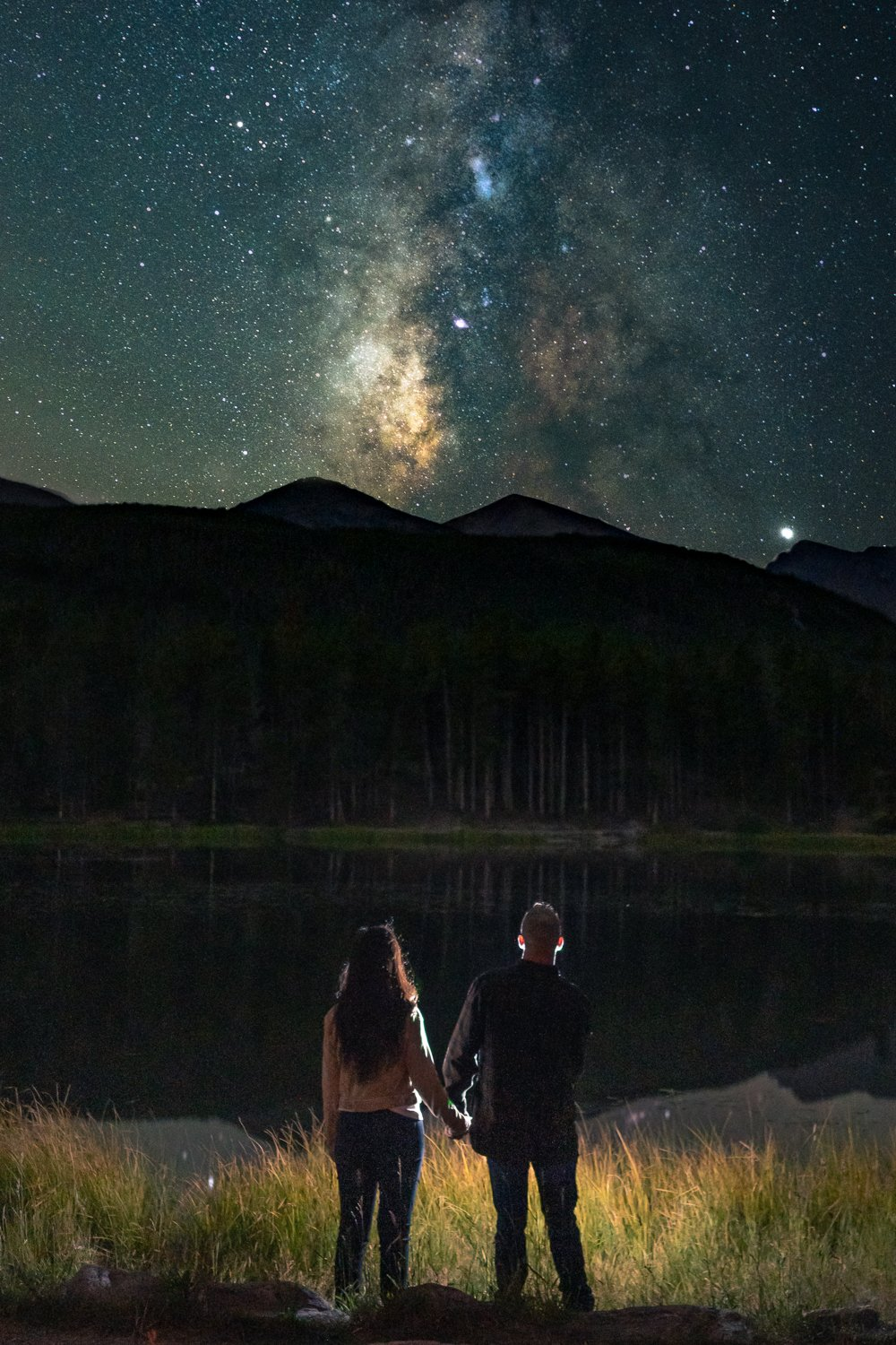 Couple stands under the milky way next to a lake for this adventurous elopement in Rocky Mountain national park
