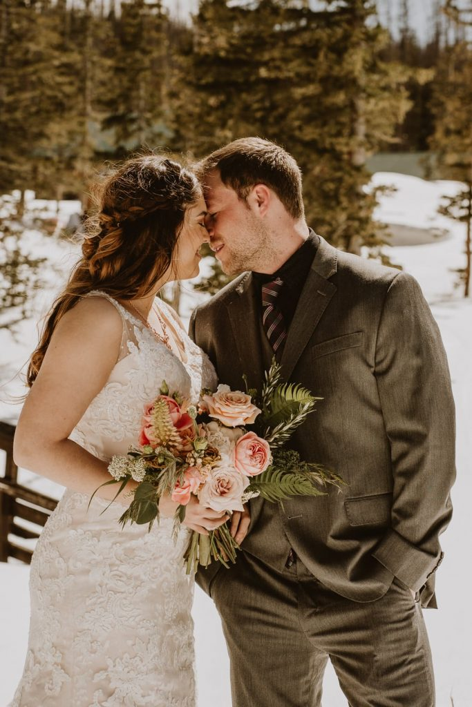 Bride and groom kiss in the snow at their sunny elopement in the Snowy Range of Wyoming.