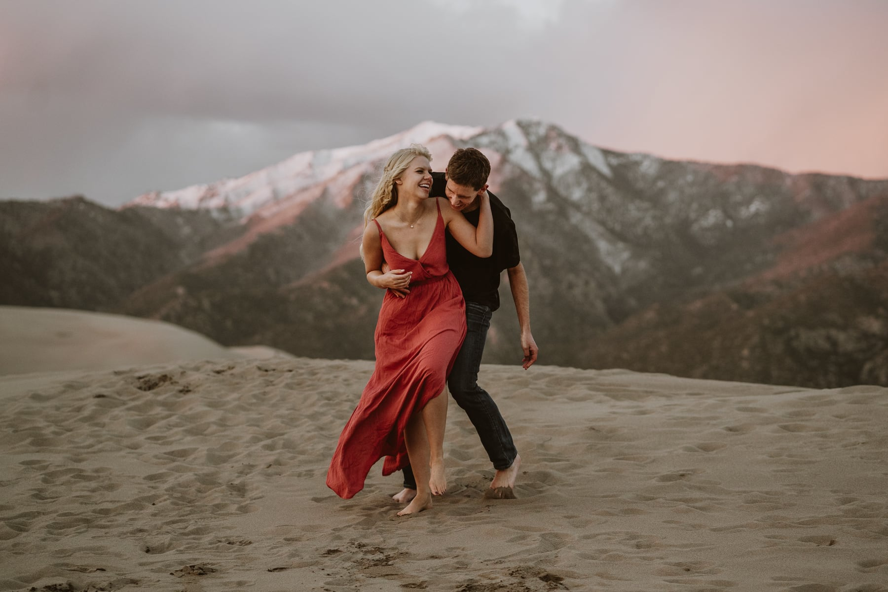 Couple dances and laughs on top of a sand dune at sunset