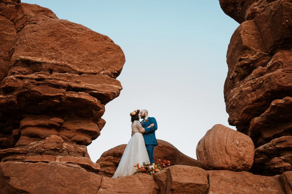 Photo of bride and groom kissing in rock formation at Garden of the Gods