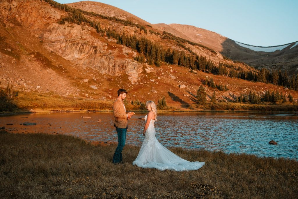 Bride and groom eloped by reading their vows at sunrise next to a lake after driving up in their Jeep