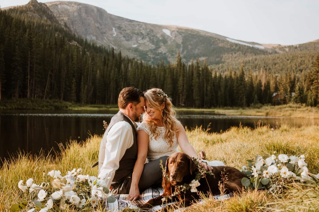 Bride and groom look into each other's eyes as they cuddle with their dog during their sunset Colorado elopement
