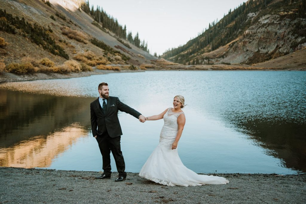 Ashley and Tim laugh as they walk across the beach in front of a calm and reflective alpine lake