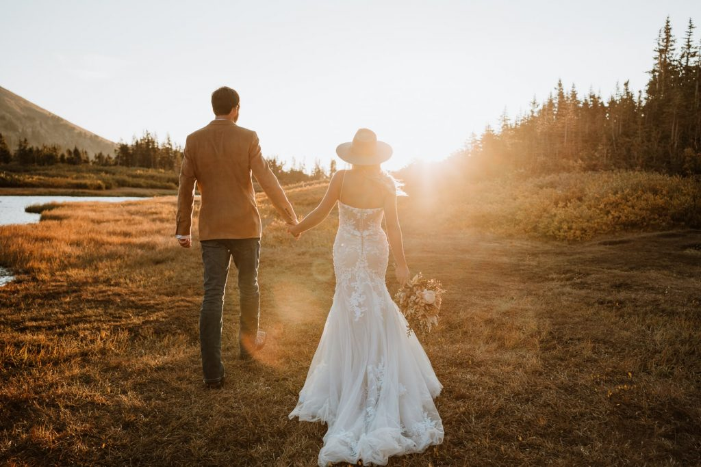 Bride and groom walk hand in hand towards the sunrise for their secluded mountain elopement