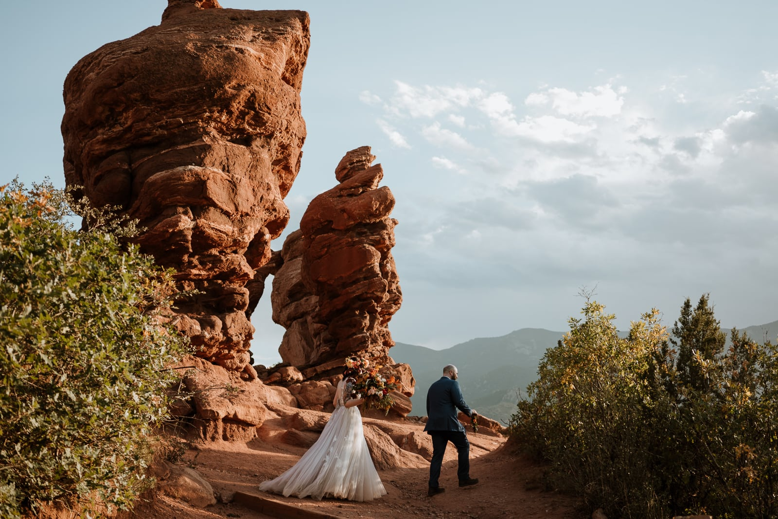 Bride and groom walking on the Siamese Twins Trail after eloping at Garden of the Gods in Colorado
