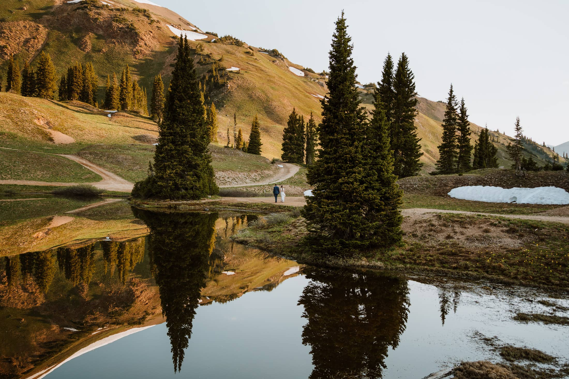Photo of bride and groom walking by a reflective alpine lake on their elopement day in Colorado. Crested Butte is one of the best locations in Colorado to elope for the views, and this photo is proof.