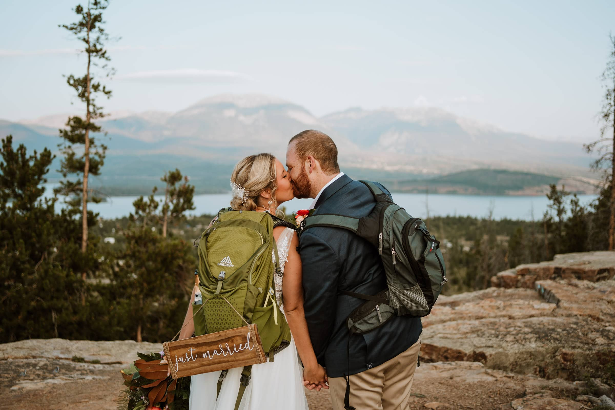 Bride and groom kiss after reading their vows at sunrise on top of a mountain peak near Breckenridge